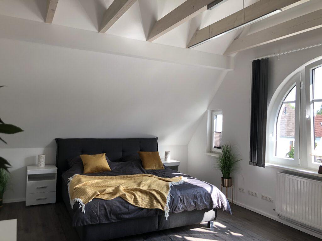 Schlafzimmer im Obergeschoss mit sichtbaren Deckenbalken